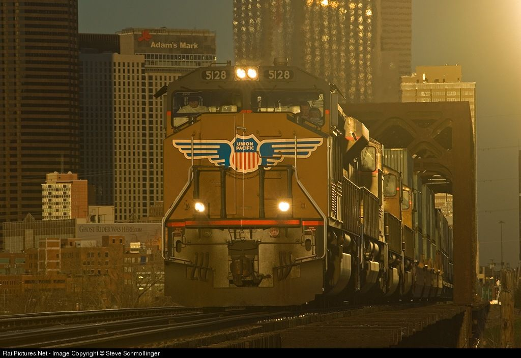 RailPictures.Net Photo: UP 5128 Union Pacific EMD SD70M at Dallas, Texas by Steve Schmollinger. UP 5128 West, a long stack train headed for the West Coast, catches the intense reflection of sunset from one of the buildings in the Dallas skyline as it crosses the Trinity River Bridge.