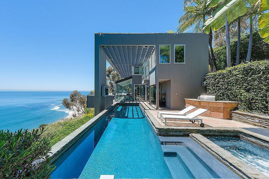 What do we have to do to get into this modern glass home, which belongs to one of our favorite Friends stars? Sliding glass walls open to the deck where a dramatic swimming pool rests next to the beach on the Malibu, CA, coastline. Source: PartnersTrust