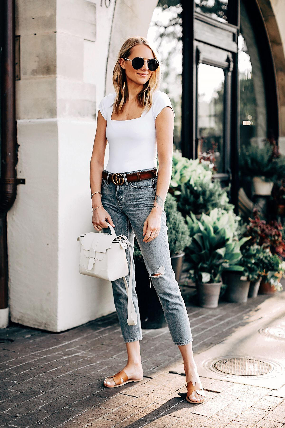 67155eddeb Blonde Woman Wearing Free People White Bodysuit Cropped Denim Ripped Jeans  Senreve Mini Maestra Cream Gucci Brown Leather Double G Belt Steven Greece  Slides ...