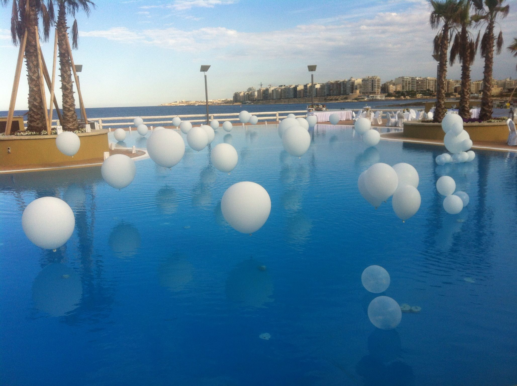 white and touch of orange balloons pool decoration | my events