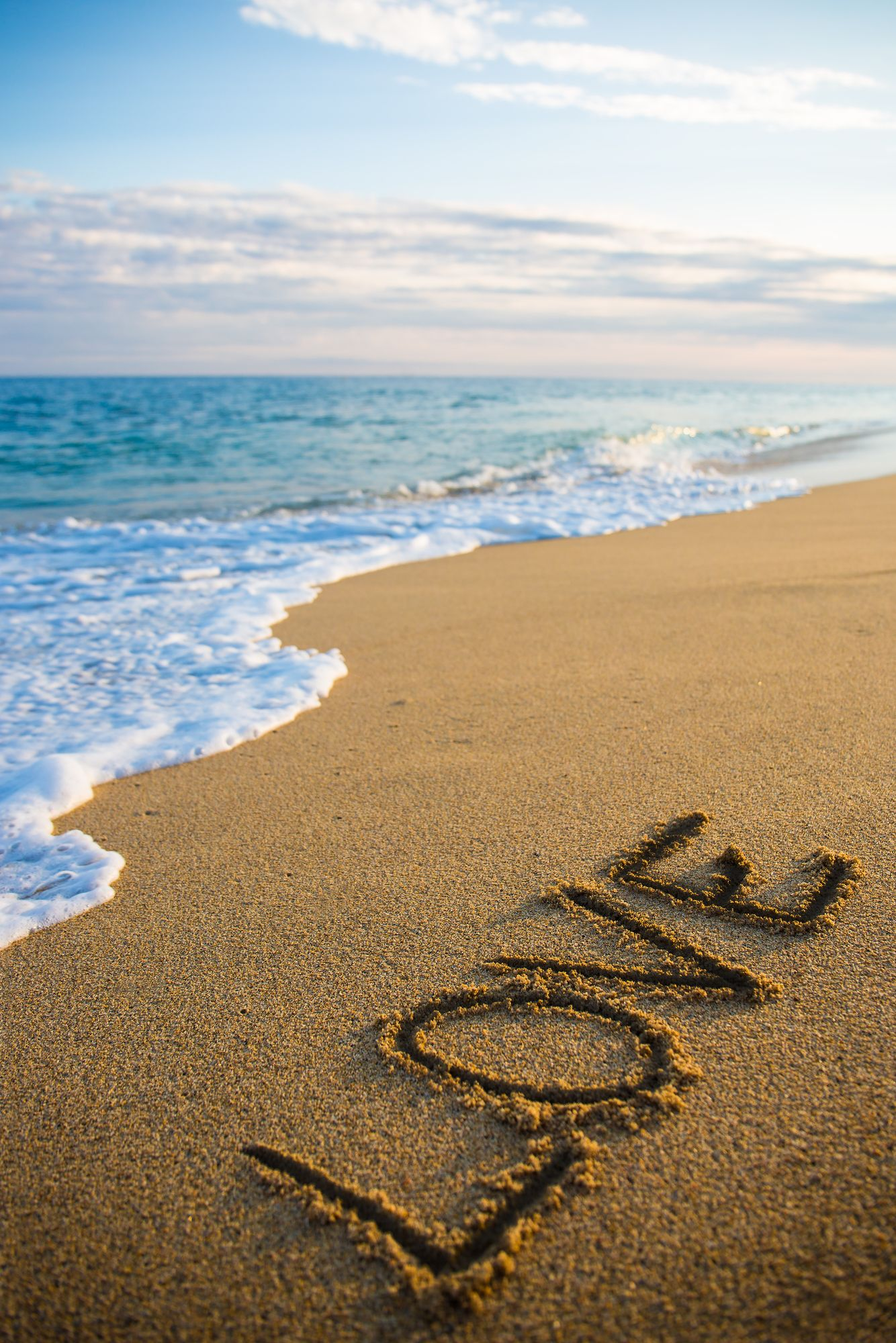 love concept beach background with word love written in sand