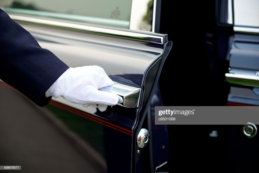 Luxury service with chauffeur opening the door Car valet
