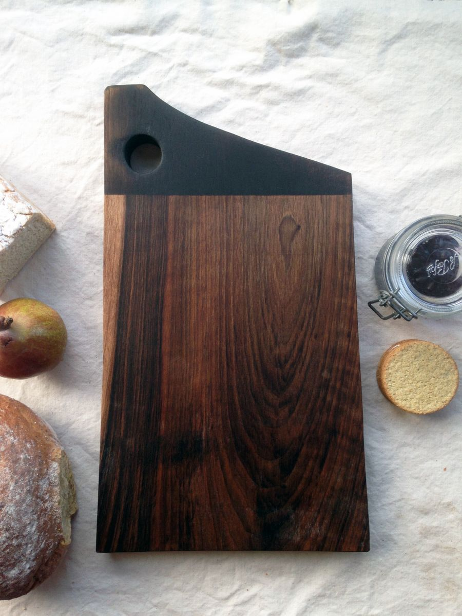 A walnut wood chopping board.Handcrafted using one piece of solid walnut, this trusty workhorse will accompany you on all of your culinary adventures, while growing more beautiful with age and use.Embellished with fire and finished with linseed oil and beeswax.44 x 25 cm approx.*Due to the nature of locally foraged wood, each board will vary in colour and grain pattern.