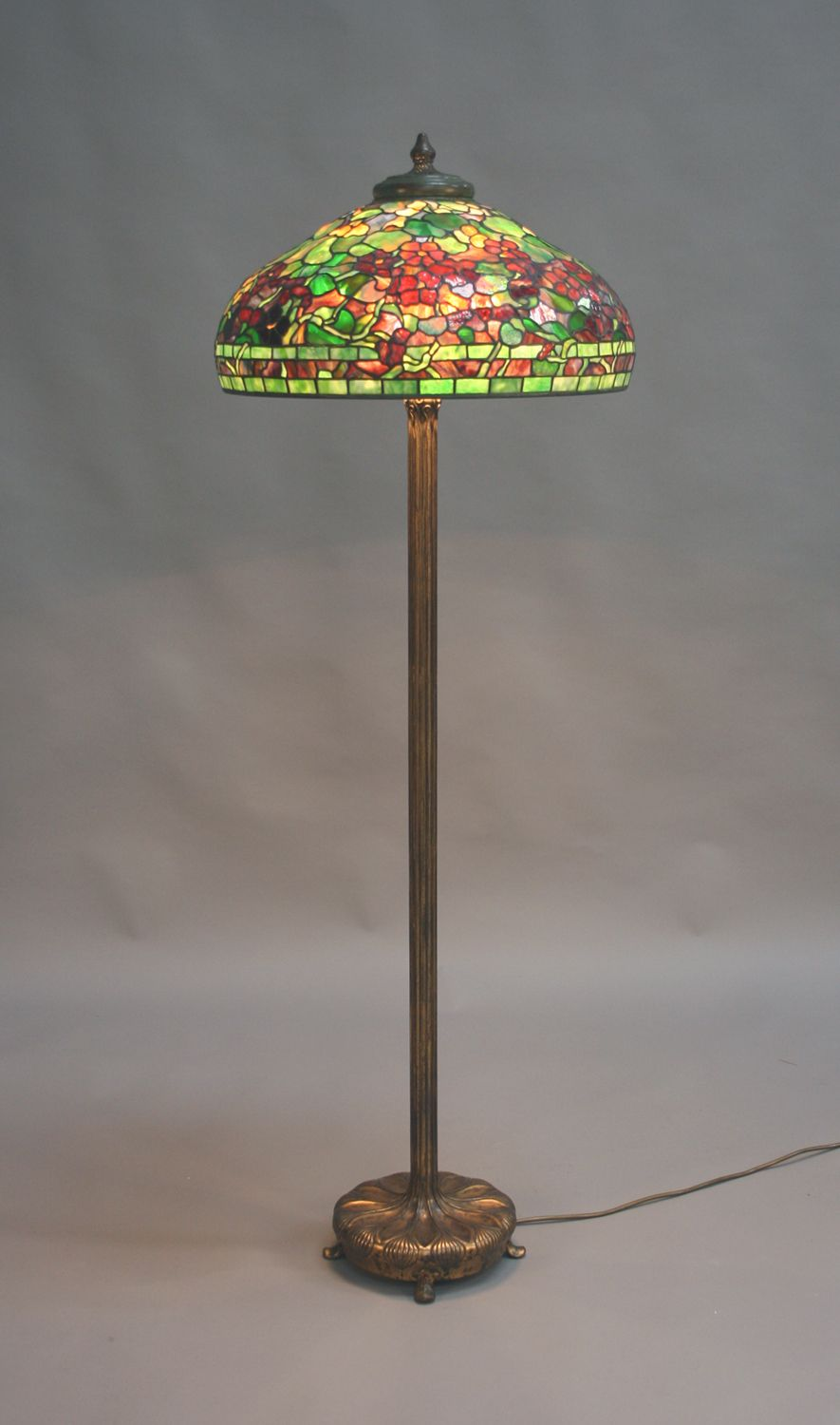 A tiffany studios nasturtium pattern green and brown patinated a tiffany studios nasturtium pattern green and brown patinated domed leaded glass shade and matched gilt bronze floor lamp circa 1910 the column base with mozeypictures Images