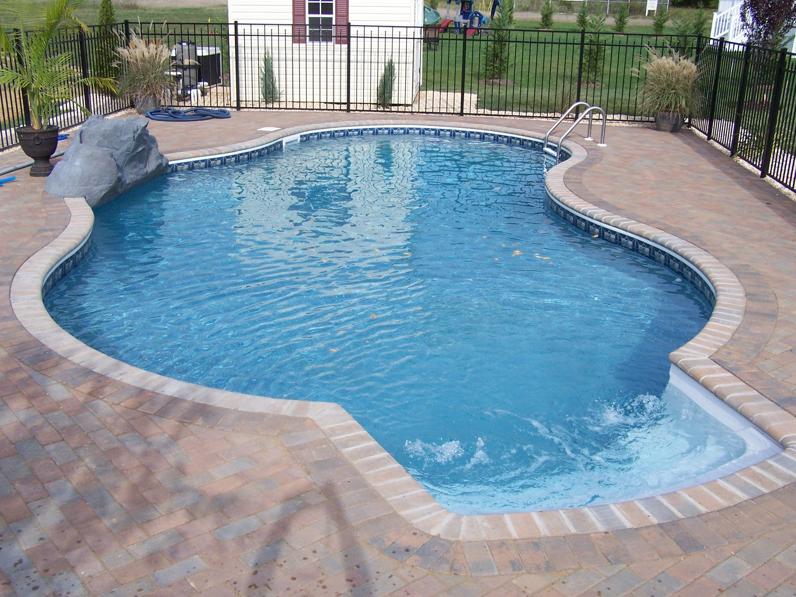Freeform with brick coping paver patio waterfall and aluminum fence our beautiful swimming for Painting aluminum swimming pool coping