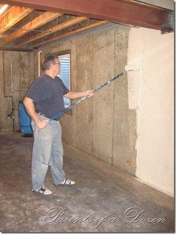 parents of a dozen painting an unfinished basement in
