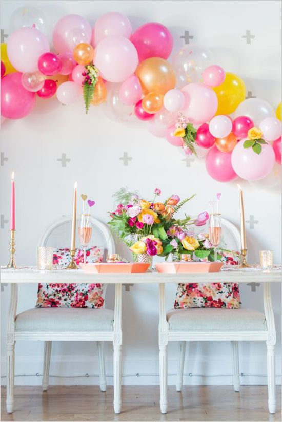 1. To create the installation I attached short pieces of yarn where the balloons were knotted and then tied them onto a long piece of yarn with a square knot. 2. I then clustered the balloons together, taped in a few posies of flowers and voila – an easy, but high impact head table backdrop!