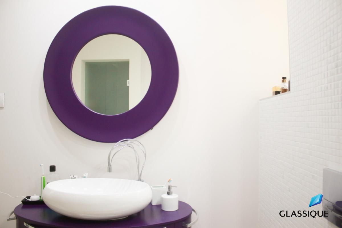 Oglindă rotundă cu ramă colorată, foarte de efect pentru o baie modernă.