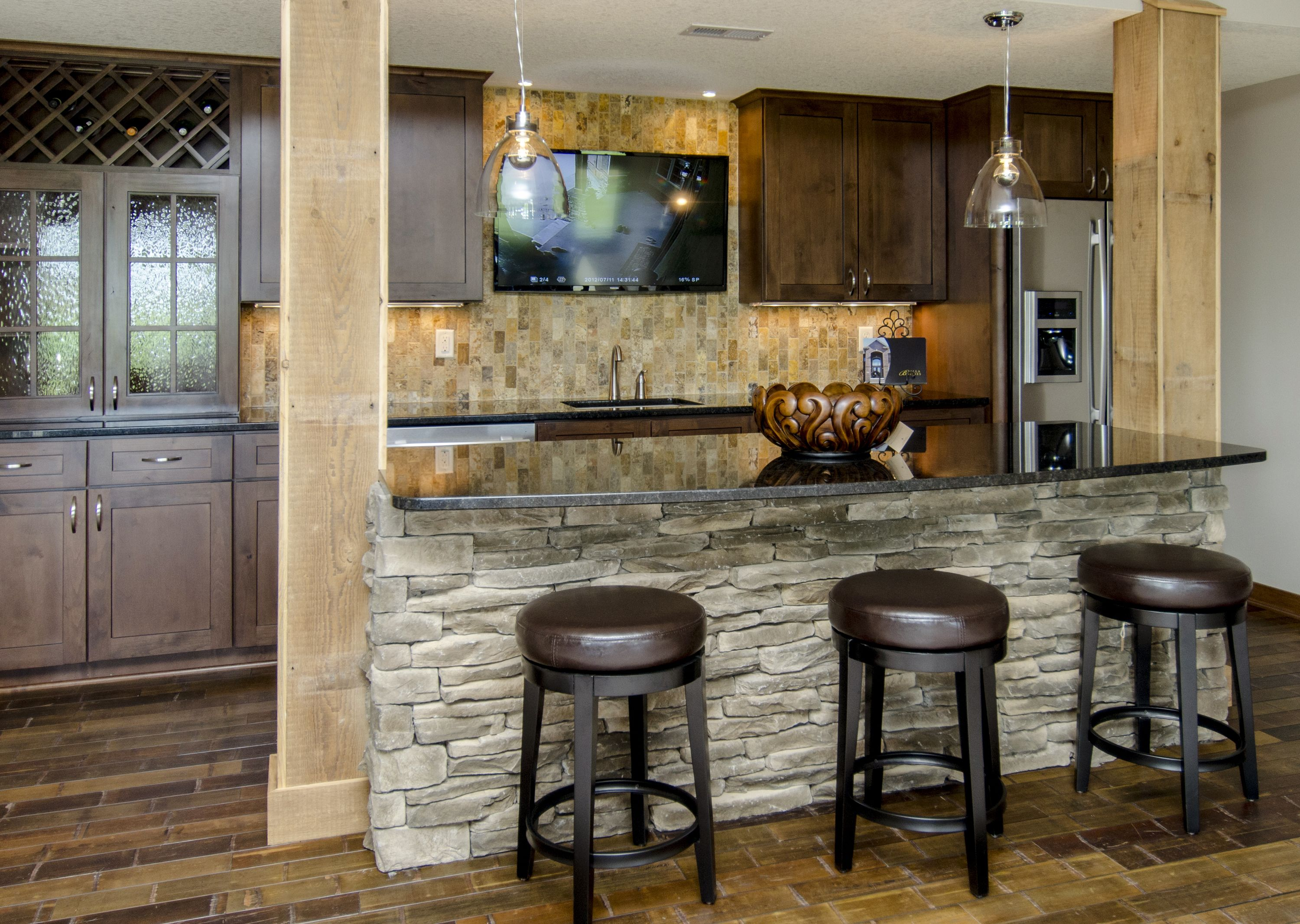 Bar Backsplash Ideas stone on bar front, wine holder, travertine backsplash, tv above