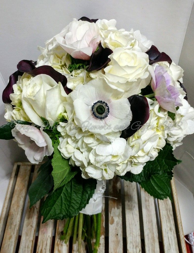 A Black And White Wedding Bouquet Of Hydrangea Anemone And Calla