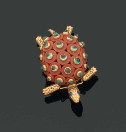 CARTIER. Années 1950. Rare brooche en forme de tortue. La carapace est formée de disques de corail piqués de cabochons d'émeraudes. Monture en or ciselé, deux cabochons de saphirs pour les yeux. Travail français.