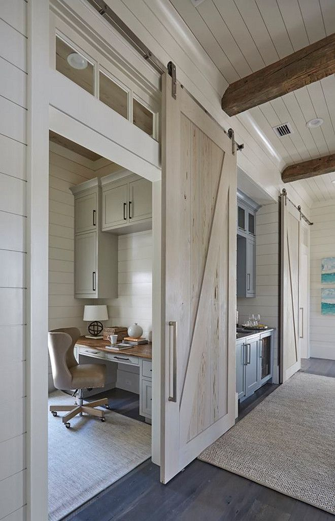 One of the pecky cypress barn door opens to reveal  home office with light gray cabinets suspended over built in desk wood top also modern farmhouse house tour new laundry room rh pinterest