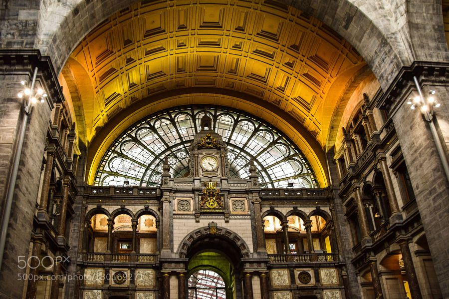 In time.... The Antwerp central station well known for it's very remarkable and beautiful architectural character. More than a 1000 people pass this clock on a daily basis usually in a hurry to catch the train. It's one of the most beautiful and impressive train stations I've even been at.