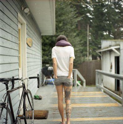 a girl, a huge leg tattoo, a bike and a yard
