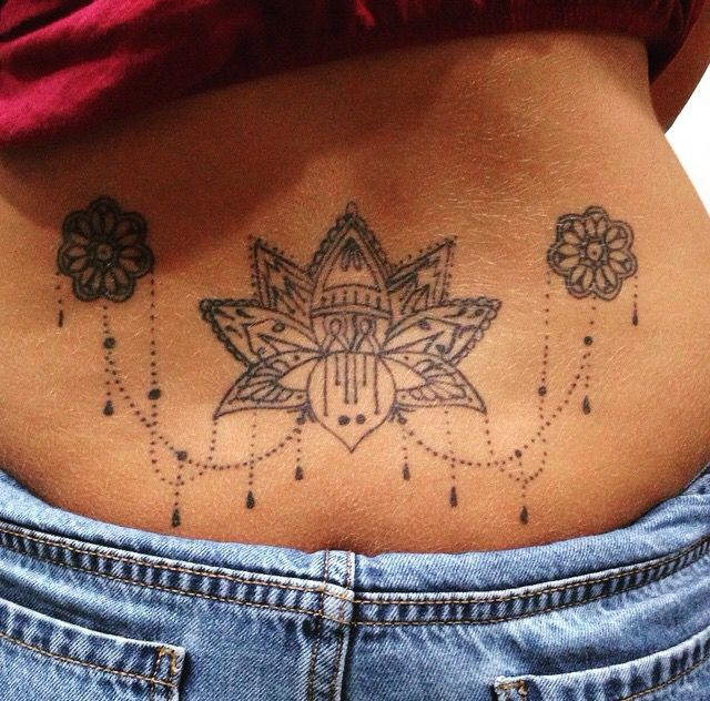 a040edbbfa0e2 Lotus flower lower back tattoo.....dont like the small ones on side but love  the placement !!