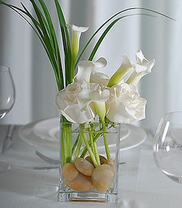Light, airy and unique centerpiece. Bear Grass, White Roses and White Mini-Callas in a short vase with rocks makes for an elegant yet charming arrangement. TO dress it up even more, consider marbles or glass rocks in the bottom of the vase.