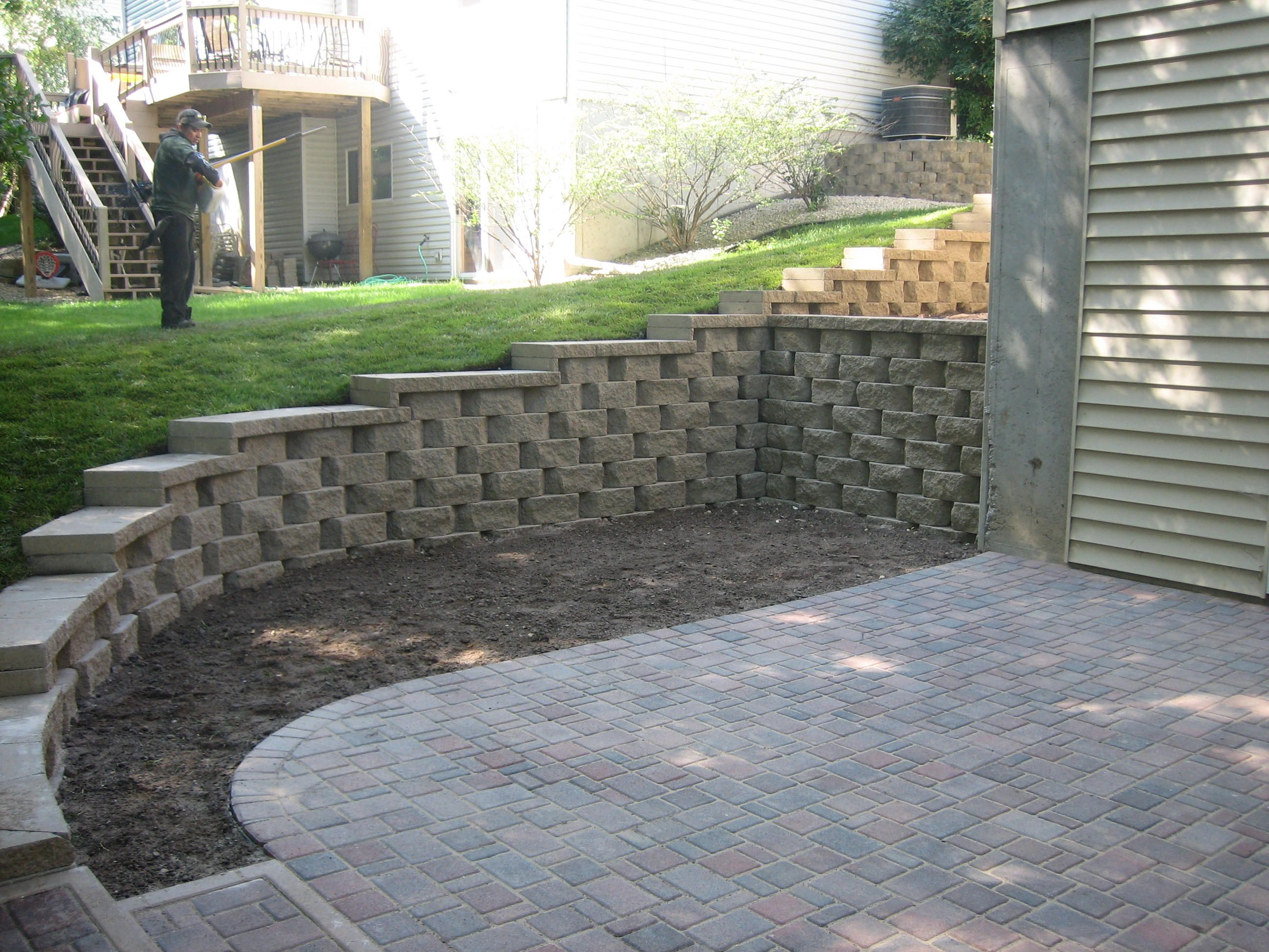 Retaining Wall With Caps And A Paver Patio Installed In Rosemount Pahl S Market Apple Valley Mn Backyard Retaining Walls Retaining Wall Patio Sloped Backyard