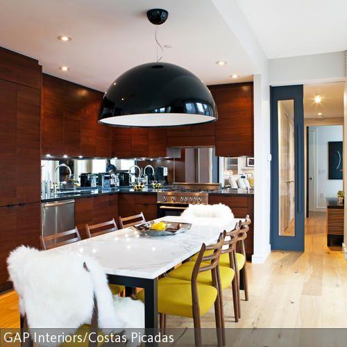 Eine opulente Leuchte eignet sich besonders gut für geräumige Essbereiche. Über der langen Tafel wird die schwarze Hängeleuchte zum Blickfang. Die dunkle Holzverkleidung …