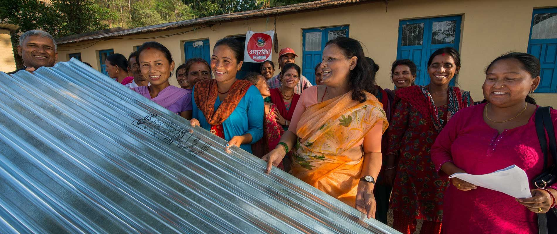 Women Awareness Center Nepal is supplying local women in Panchkl Pipaldanda, Kavre, with sheets of zinc-corrugated tin for rebuilding homes  and shelters, with funds from Global Fund for Women. Here, Women Awareness Center Nepal founder Prativa Subedi (second from right), joins other women in lifting up one of the sheets.