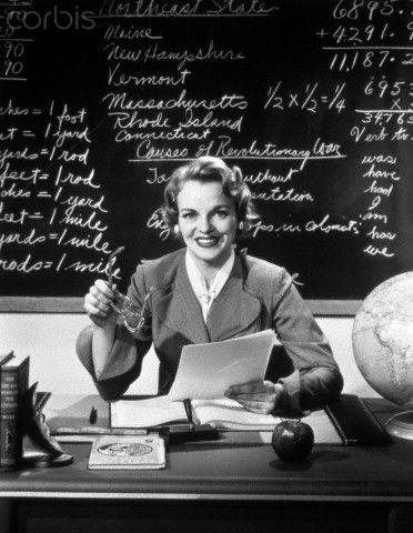 1950s Smiling Woman Elementary School Teacher Sitting Behind Desk In Front Of Blackboard Looking At Camera