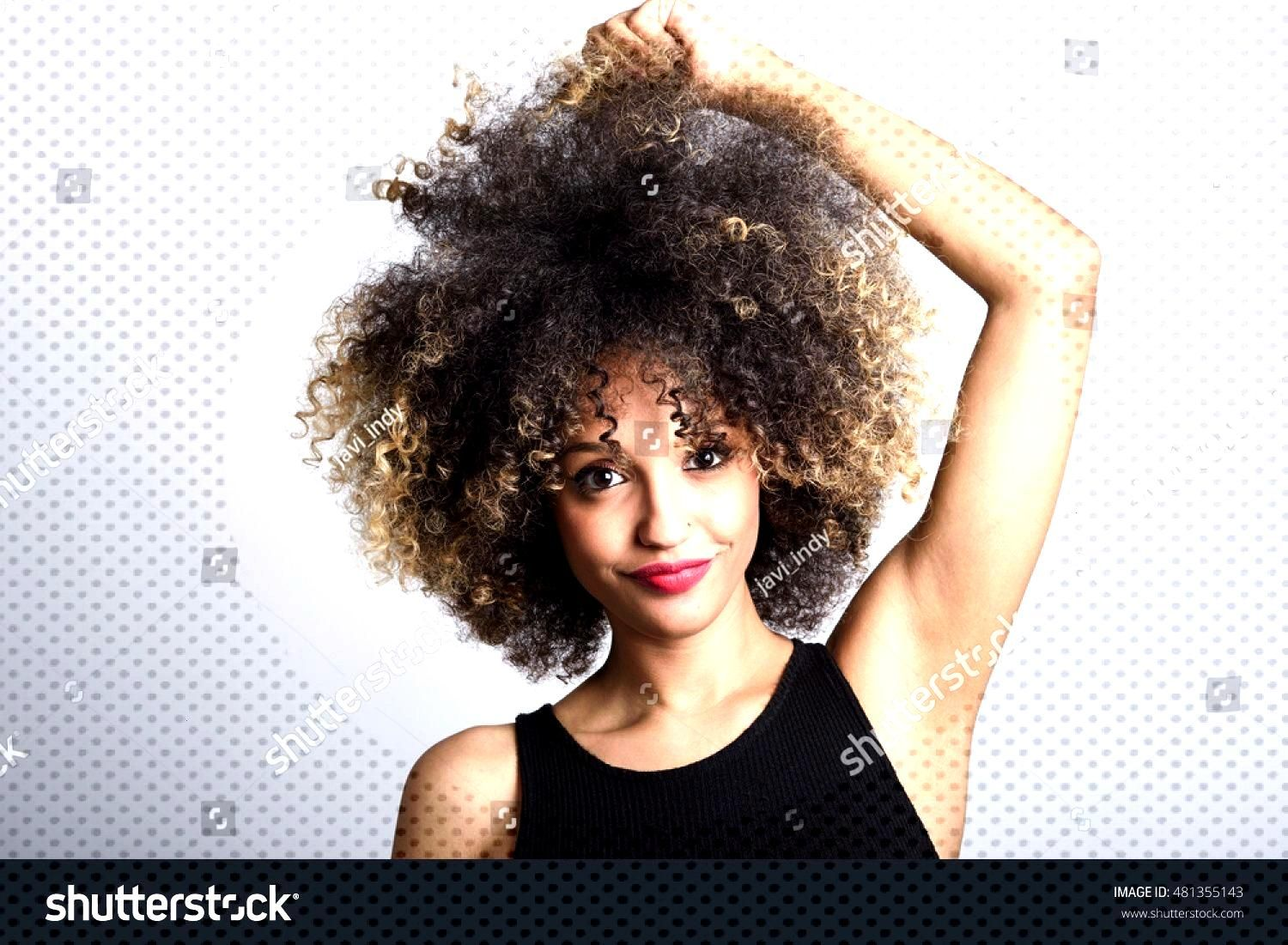 Young black woman with afro hairstyle smiling. Girl wearing black dress. Studio shot. ,