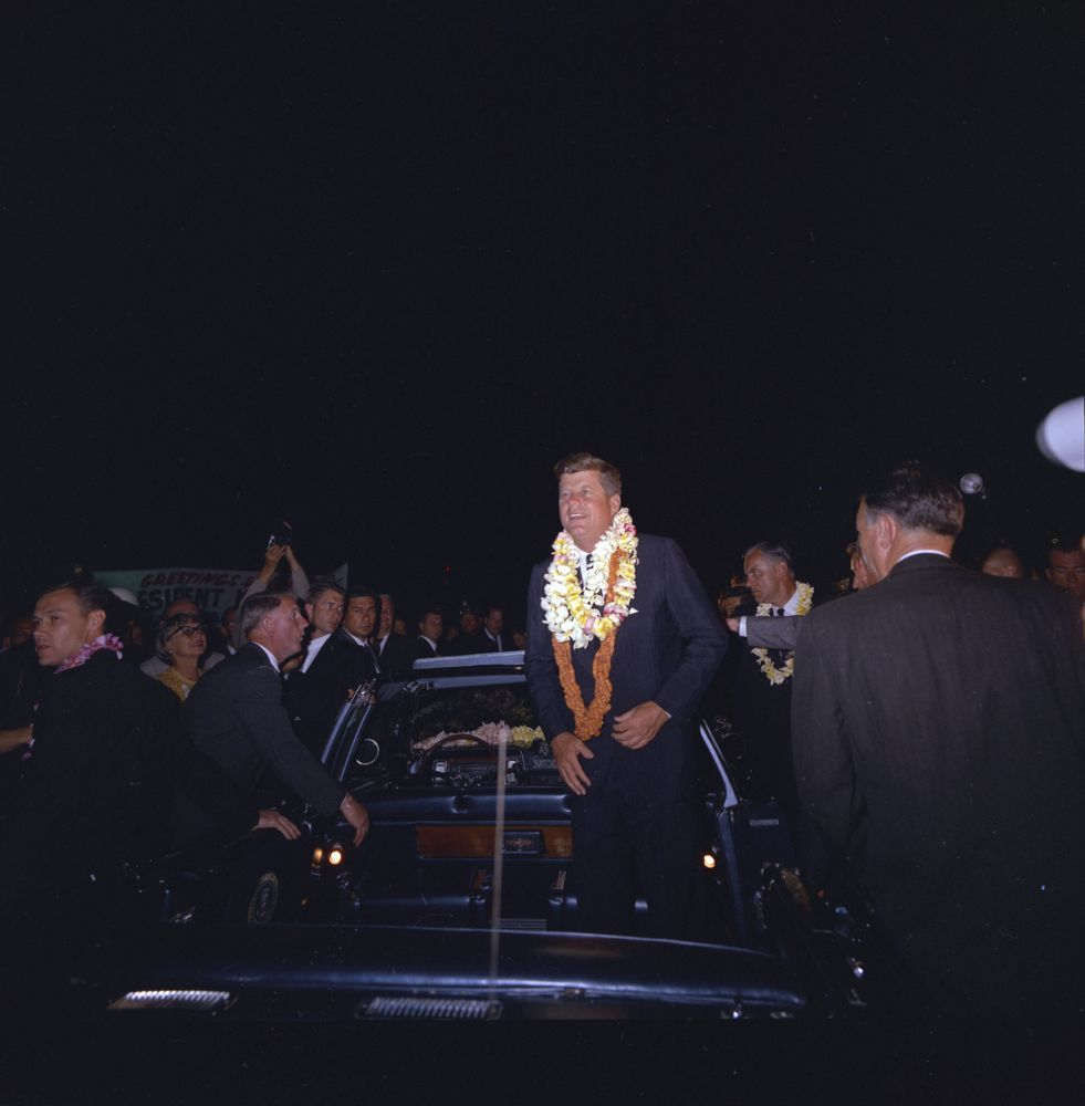 June 8, 1963 President John F. Kennedy (wearing flower leis) stands in the…
