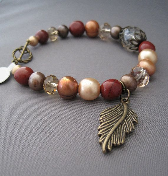 Brass Feather Bracelet is Red, Orange and Brown tones by sea chelles design