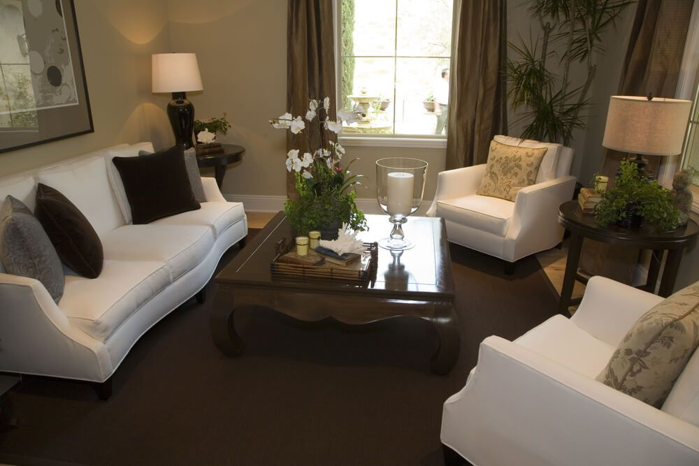 Centered Around A Polished Square Traditional Coffee Table This Living Room Features Living Room Carpet Brown Carpet Living Room Furniture Design Living Room