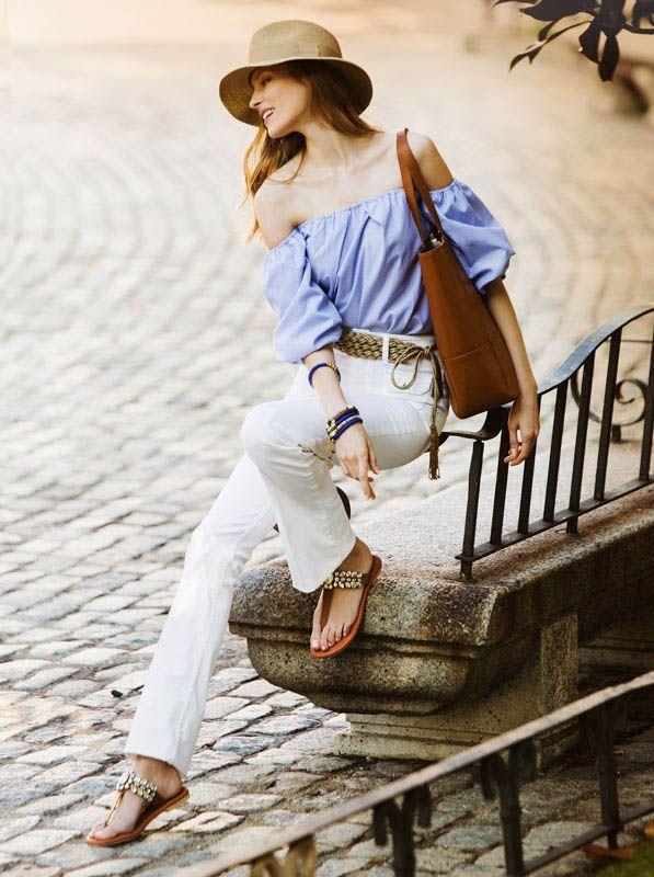 Camisa Off shoulder en azul combinada con pantalón blanco y sandalias de piedras.