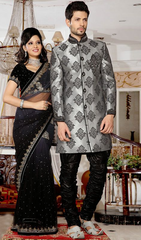 Look handsome and elite dressed in this black and silver brocade indo western sherwani. The attractive lace, moti, resham and stones work a considerable attribute of this attire. Brocade might vary from actual image. #Men'sSherwani