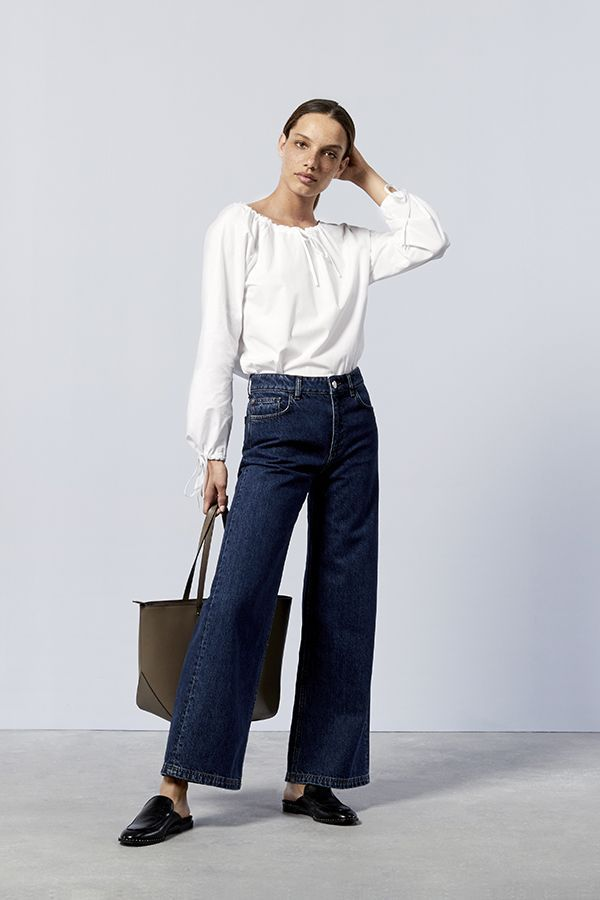 Trendy yet ageless stying in flared jeans, white blouse and slippers