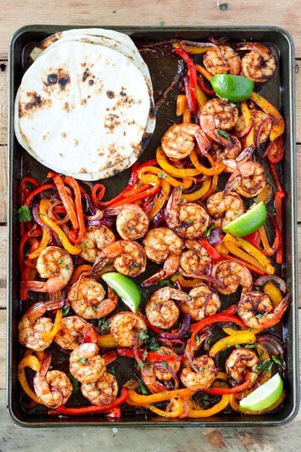 We love seafood sheet pan recipes for easy prep, delicious results, and quick clean-up. Today we are featuring Spicy Sheet Pan Salmon, Sheet Pan Garlic Butter Tilapia, Easy Sheet Pan Shrimp Fajitas, and Sheet Pan Honey Mustard Salmon and Rainbow Veggies. #sheetpan #dinner #recipe #inspo #seafood #salmon #shrimp #tilapia #rainbow #veggies #yum
