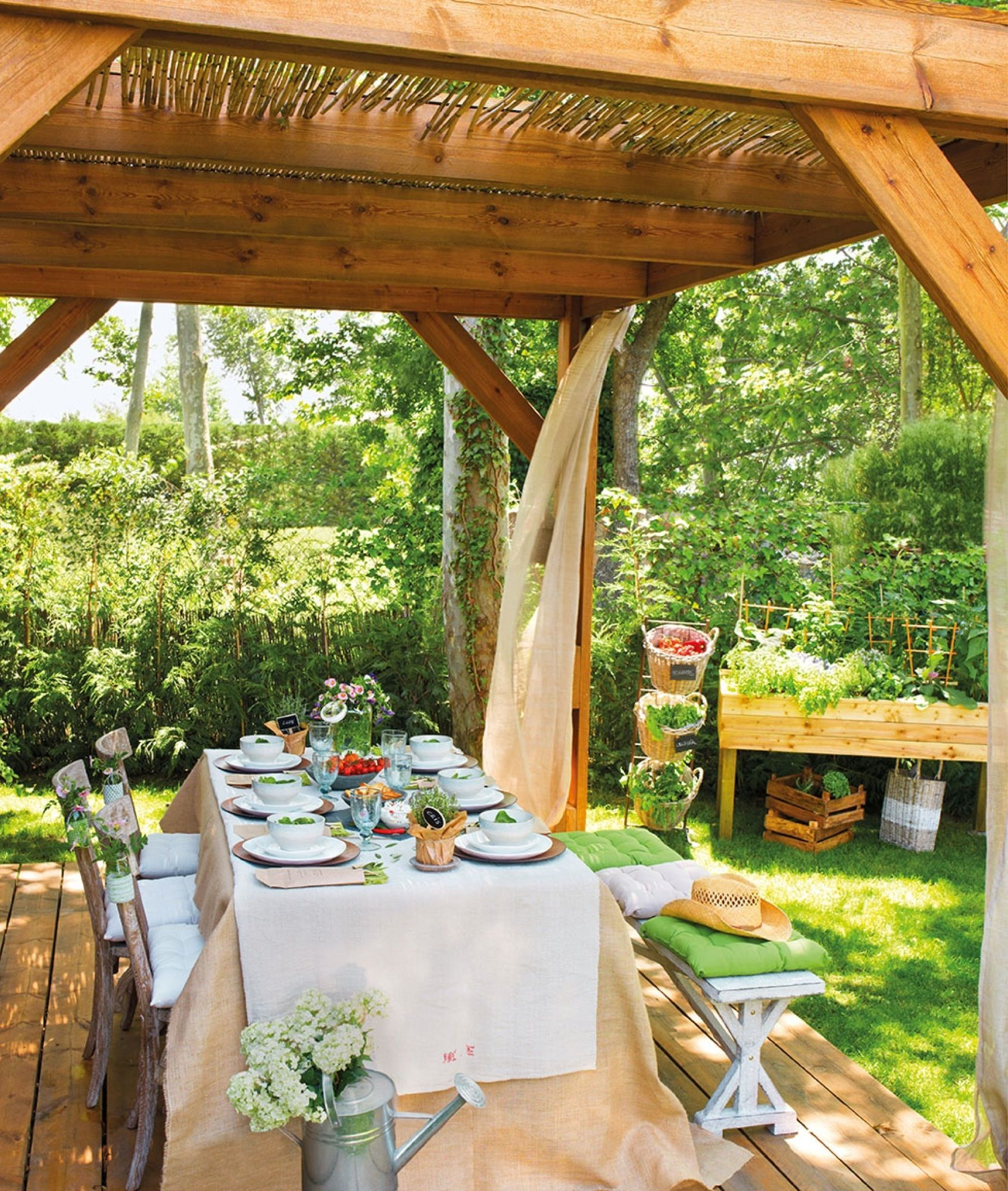 Comedor bajo p rgola de madera y ca as con cortinas y for Patios y jardines
