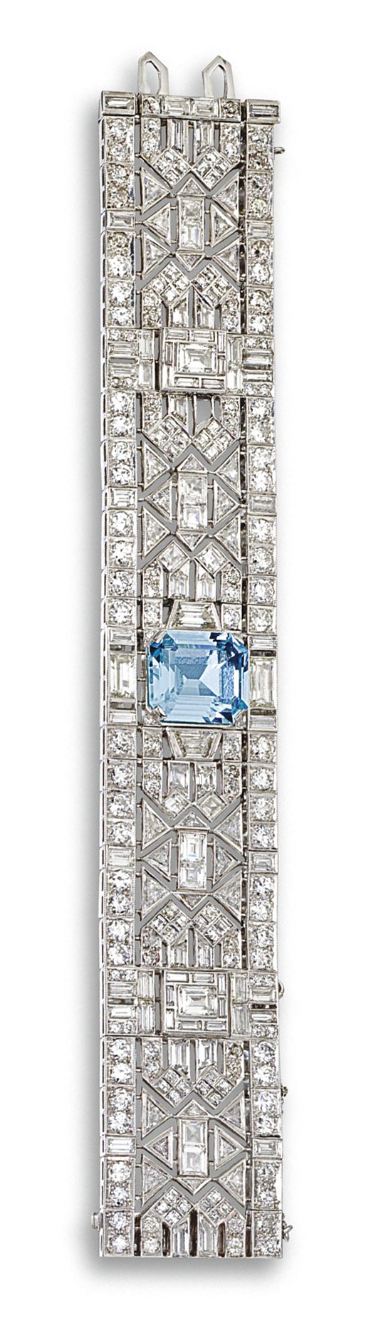 AQUAMARINE AND DIAMOND BRACELET, CIRCA 1935. The wide articulated band of open geometric design set with 102 old European-cut, 106 baguette, 32 triangular-shaped, and 20 whistle-cut, trapeze-cut and emerald-cut diamonds, altogether weighing approximately 43.00 carats, the center set with an emerald-cut aquamarine of approximately 13.75 carats, mounted in platinum