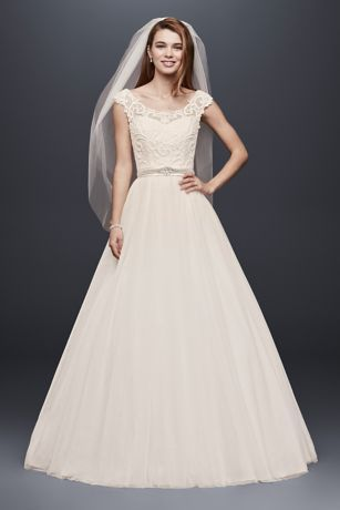 0cef853469f5 The scroll lace that adorns the bodice of this classic tulle ball gown  creates an elegant pattern that partners beautifully with the illusion cap  sleeves.
