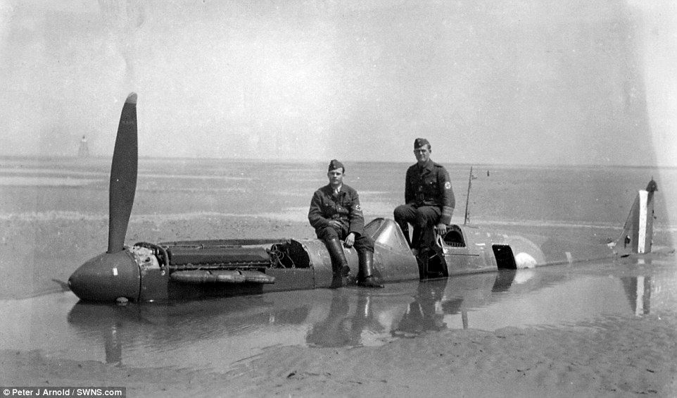 Beached: German soldiers sitting on the Spitfire brought down on the wet sands at Calais by Flying Officer Peter Cazenove. It had been hit by a single bullet from a German Dornier bomber.The plane was consumed by the sandy beach and remained there for 40 years