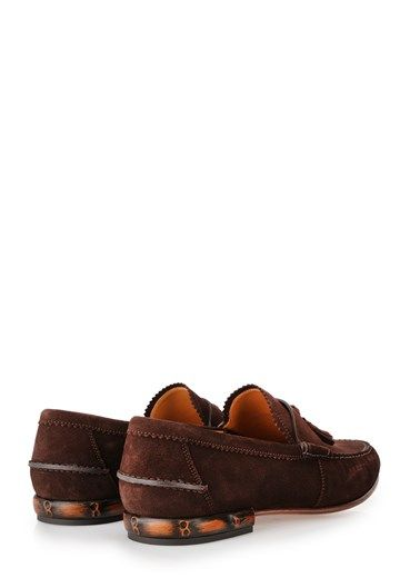 Brown suede moccasin with tassels detail by Gucci with visible stitching, leather sole and bamboo covered heel.