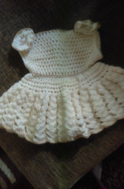 A white and gold baby dress with designs and hand made with flowers