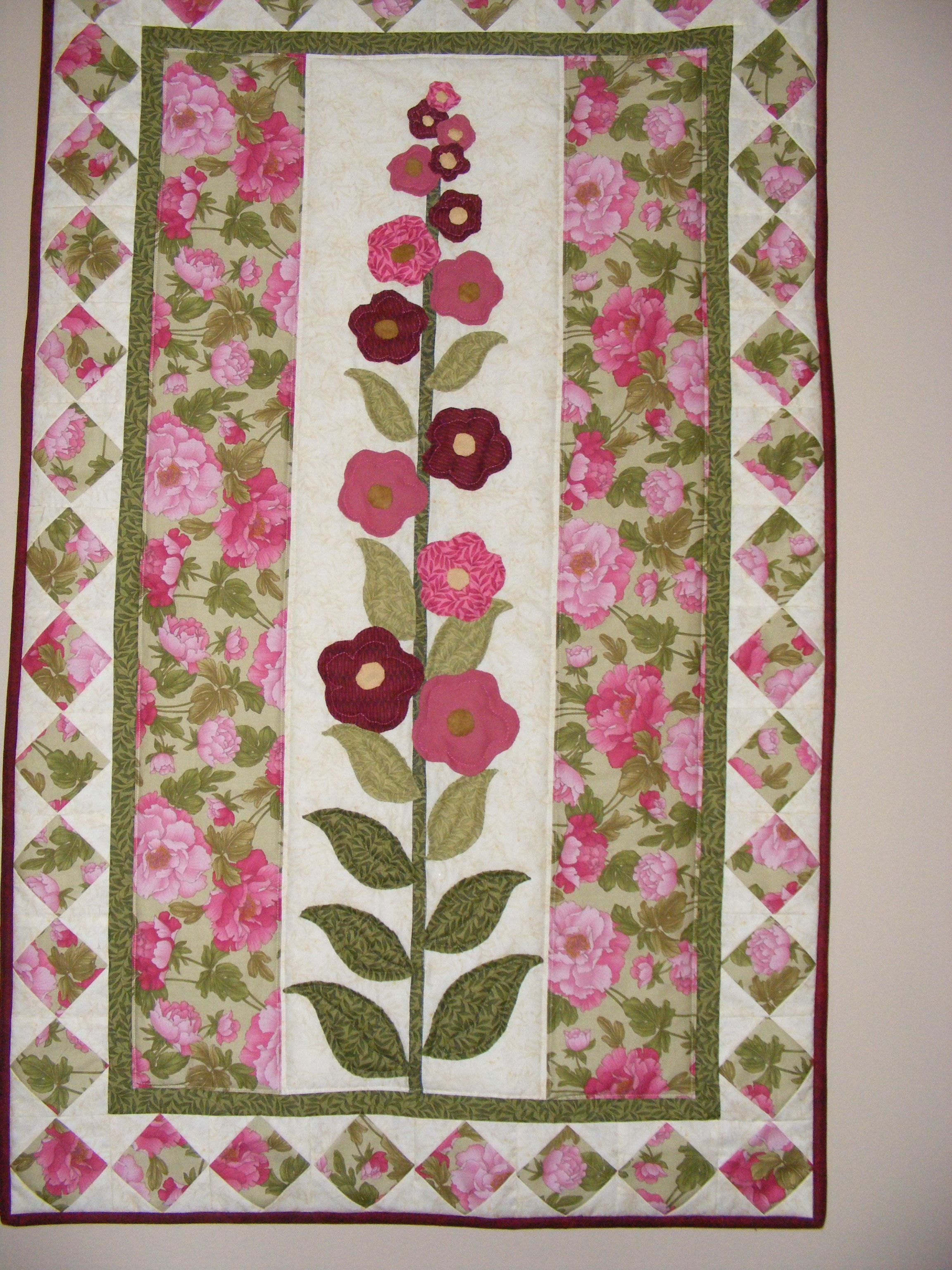 I first made this using wonder-under but I thought it looked rather flat and dull.  I ripped all the flower and leaves off and re-did it using traditional needle turn applique and I love it!