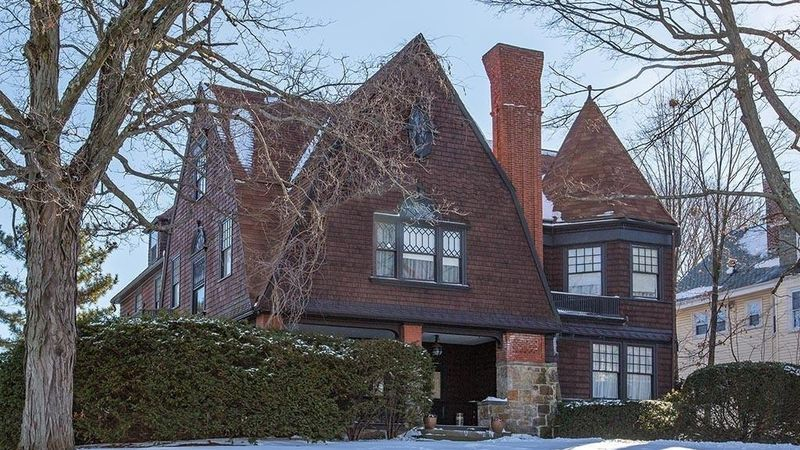 This shingle style house in Brighton, MA has a stone base, dark wood shingles, peaked roofs, a corner tower, covered porch, ornate windows, and a brick chimney.