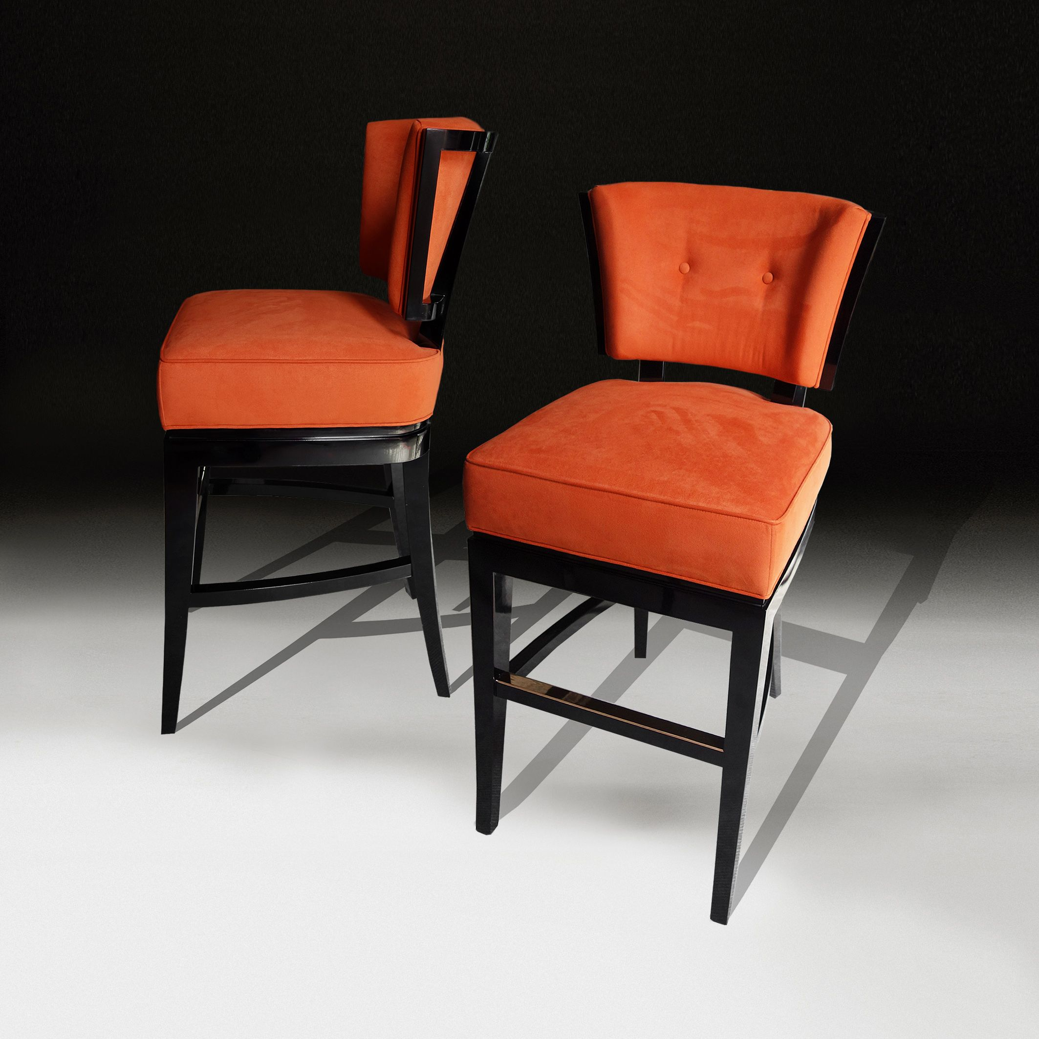 Bar stools in burnt orange suede with a black lacquer frame and bronze foot