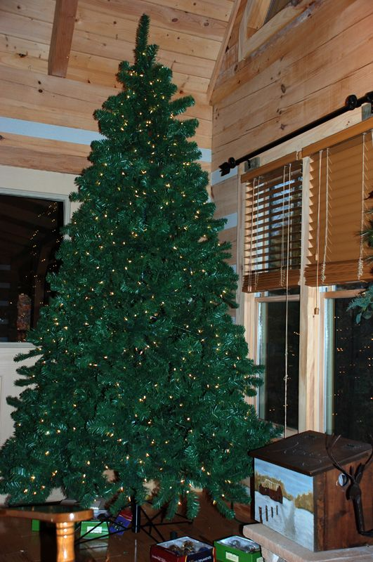 A Minimally Decorated Christmas Tree Inside A Log Home.