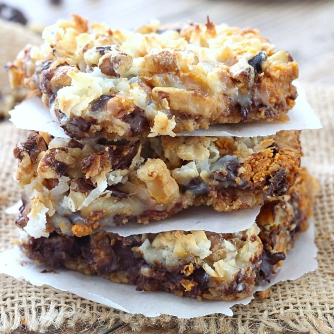 Seven Layer Magic Bars – A buttery graham cracker crust is topped layers of chocolate chips, butterscotch chips, coconut, chopped nuts, and then finished off with a blanket of sweetened condensed milk. These will not last long! . Get the recipe at  or click the link in bio. . Hashtag if you make this recipe. .