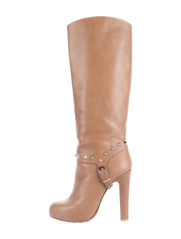 Light brown leather Valentino round-toe Rockstud knee-high boots with gold-tone hardware featuring pyramid stud embellishments at ankles and buckle accent at sides, tonal stitching throughout, concealed platforms and covered heels. Includes dust bag.