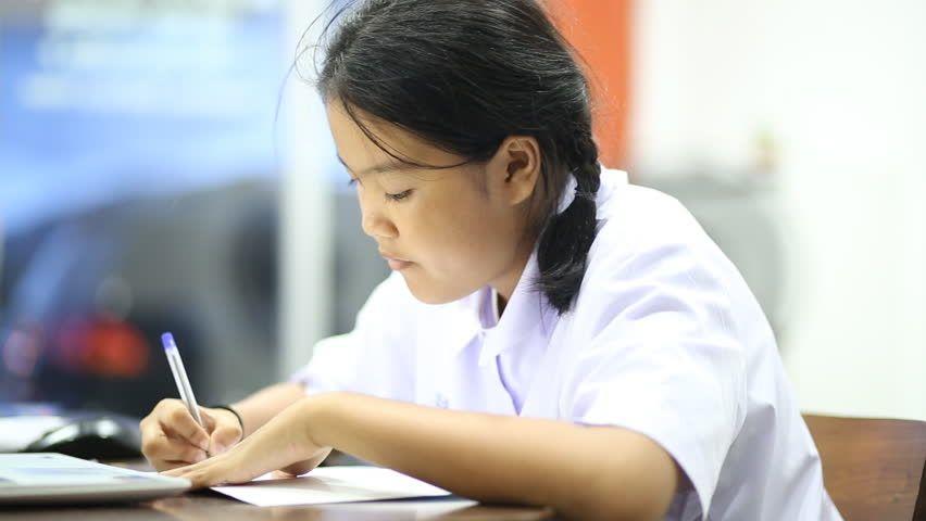 Ad: Une élève asiatique faisant ses devoirs, une jeune femme asiatique assise dans …