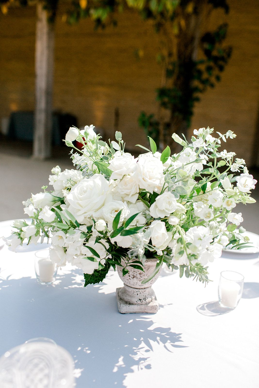Round Table Centerpiece Stone Compote With White Flowers And Eucalyptus Greener White Wedding Centerpieces White Floral Centerpieces Table Flower Arrangements