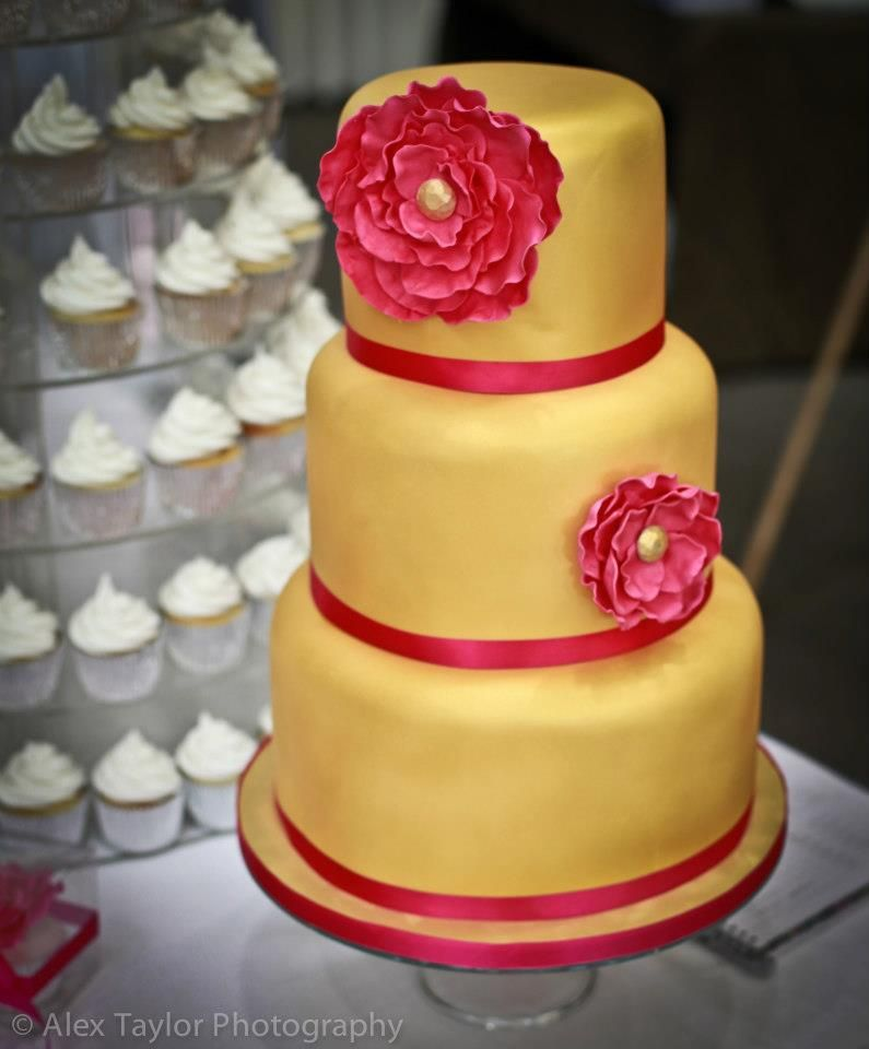 Gold wedding cake with hot pink flower from http://swirlsbakery.co ...