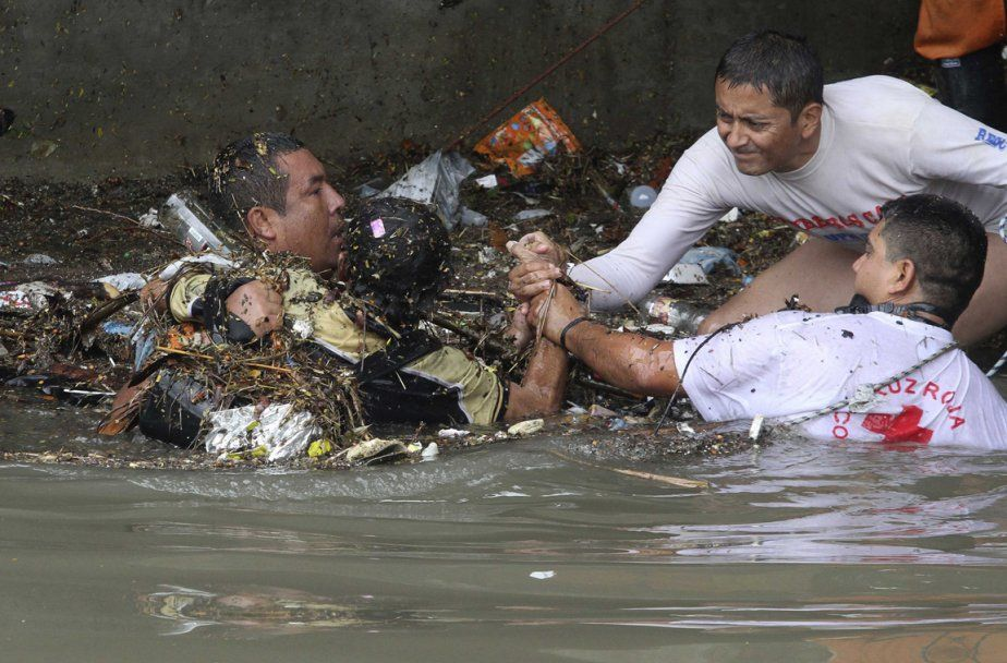 JAIME SALDARRIAGA (REUTERS)  Des secouristes tentent de porter aide à une victime de l'inondation à Cali en Colombie.