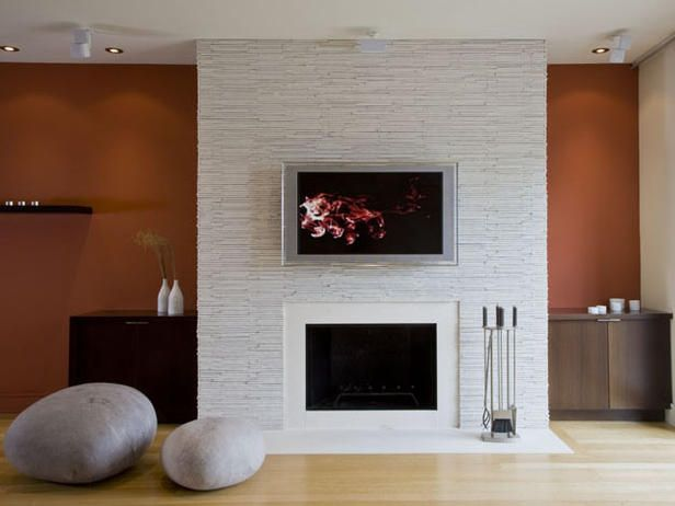 The Stone Mass Of The Fireplace Against The Burnt Orange Wall The Dark Wenge Cabinetr Fireplace Design Contemporary Fireplace Designs Stacked Stone Fireplaces
