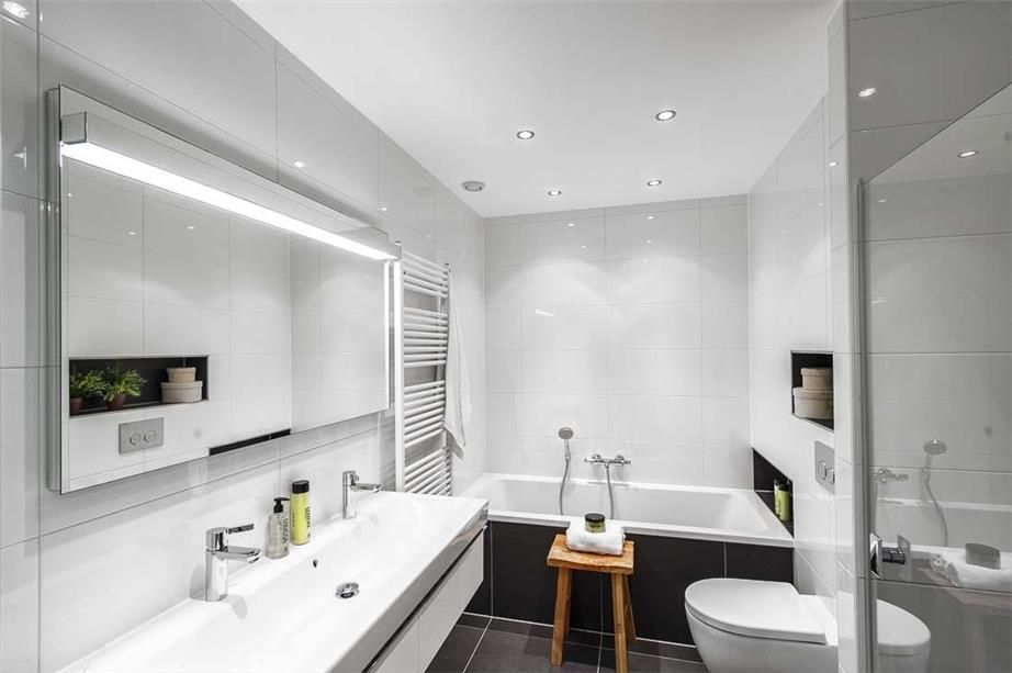 Kleine badkamer met dubbele wastafel, ligbad, nissen en een ...